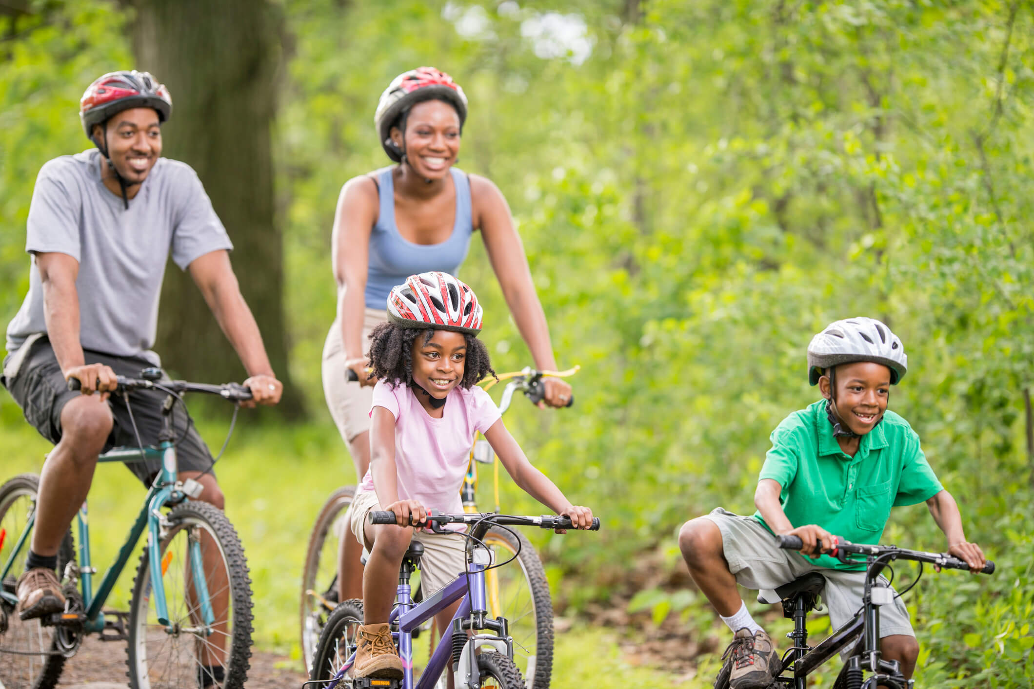 A family is going on a bike ride through the woods while on summer vacation.