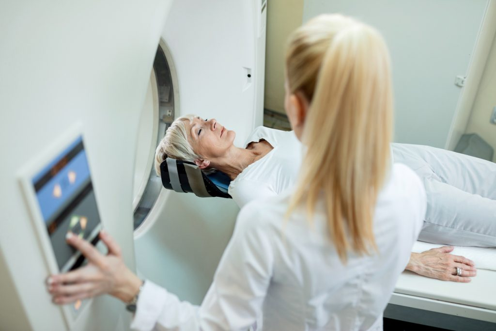 Senior women radiologist during MRI scan examination at clinic.