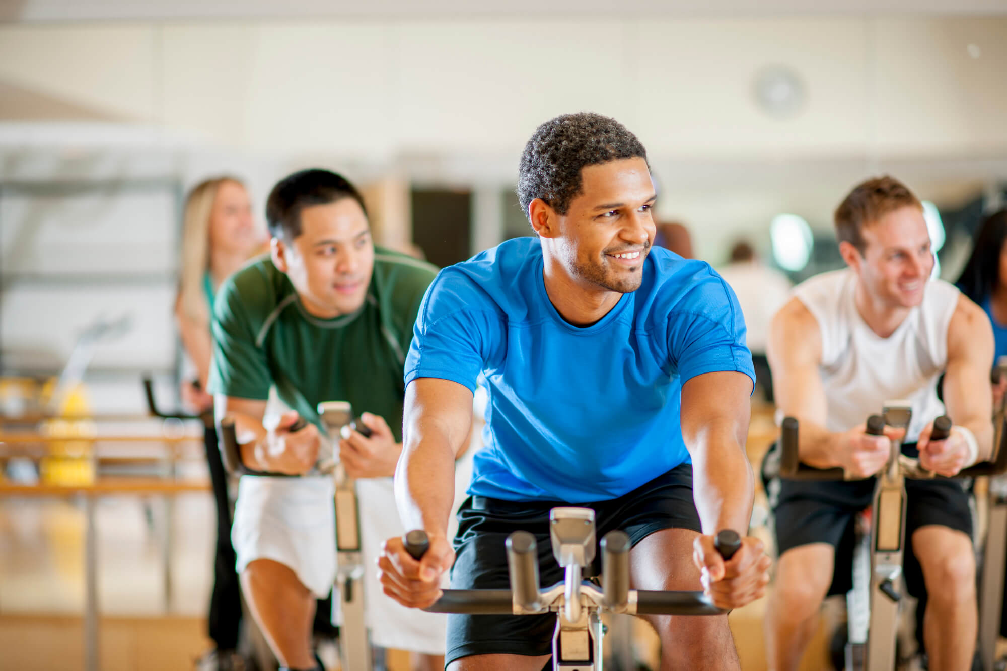 A multi-ethnic group of young adults are working out at the gym by taking a cycling spin class.